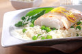 Healthy meal of baked fish rice and peas fillet garnished with fresh lemon zest served on a white plate Royalty Free Stock Images