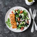 Healthy mediterranean lunch - grilled fillet salmon and vegetables, olives, feta greek salad on dark background, top view Royalty Free Stock Photo