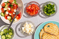 Healthy mediterranean salad with toast preparing a dish of fresh ingredients in bowls including tomato cucumber feta cheese and Stock Photos