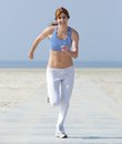 Healthy middle aged woman enjoying a jog full length portrait of at the beach Stock Image