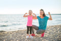 Healthy mother and baby girl showing biceps on bea Royalty Free Stock Photo