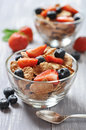 Healthy muesli and fresh berries glass bowl with on a wooden background Royalty Free Stock Photos