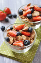 Healthy muesli and fresh berries glass bowl with on a wooden background Royalty Free Stock Photo