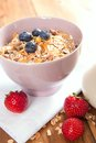 Healthy muesli with fresh berries and milk a bowl of on the table Stock Photography