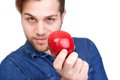 Healthy nutritious diet portrait of a young man holding red organic apple showing Stock Image