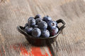 Healthy ripe autumn blueberries in a ceramic dish on an old rustic wooden picnic table for a delicious snack Stock Photo
