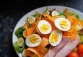 Healthy salad of boiled eggs, ham, tomatoes, carrots, etc. on black granite worktop Royalty Free Stock Photo