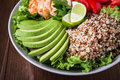 Healthy salad bowl with quinoa, tomatoes, chicken, avocado, lime and mixed greens, lettuce, parsley Royalty Free Stock Photo