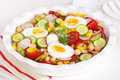 Healthy salad hard boiled eggs chickpeas tomatoes radishes green onions cucumber yellow capsicum lemon vinaigrette dressing Stock Photo
