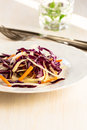 Healthy salad with red cabbage and carrot green on white plate Stock Photo