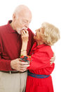 Healthy senior couple eating berries fit wife is feeding a strawberry to her husband isolated on white Stock Images