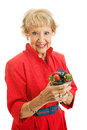 Healthy senior woman with berries beautiful in her eighties holding a bowl of beautiful fresh isolated on white Stock Image