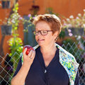 Healthy senior woman eating a red apple in glasses standing outdoors in her garden holding it up in her hand with look of Royalty Free Stock Image