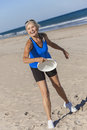 Healthy senior woman playing frisbee at beach fit and with on a deserted by the sea Stock Image