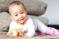 Healthy smiling baby girl with apple in hands nine months old loved on bed having an her Royalty Free Stock Photo
