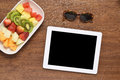 Healthy snack and tablet on wooden desk Royalty Free Stock Photo