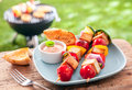 Healthy summer meal of halloumi kebabs and vegetable roasted over an outdoor barbeque in the garden and served with a savory sauce Stock Image