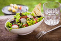 Healthy summer salad with a glass of fresh water lettuce bell pepper tomato and radish served on rustic wooden garden table Stock Photos