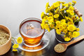 Healthy tea in glass cup closeup, bucket with coltsfoot flowers Royalty Free Stock Photo