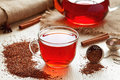 Healthy traditional herbal rooibos beverage tea cup of red with spices on vintage wooden table Stock Photos