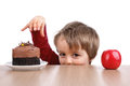 Healthy unhealthy eating little boy choosing cake apple Royalty Free Stock Photo