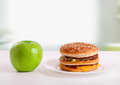 Healthy, unhealthy food. Diet concept: apple, ha Stock Photography
