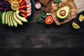 Healthy vegan food concept. Healthy food with vegetables and whole wheat bread on the wooden table top view. Copy space