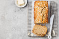 Healthy vegan oat and coconut loaf bread cake on a cooling rack top view copy space grey stone background Stock Photography