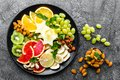 Picture : Healthy vegetarian bowl dish with fresh fruits and nuts. Plate with raw apple, orange, grapefruit, banana, kiwi, lemon, grape, alm  collection pie