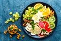 Healthy vegetarian bowl dish with fresh fruits and nuts. Plate with raw apple, orange, grapefruit, banana, kiwi, lemon, grape, alm Royalty Free Stock Photo