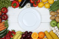 Healthy vegetarian eating vegetables and fruits on empty plate Royalty Free Stock Photo
