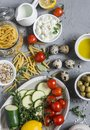 Healthy vegetarian food ingredients - pasta, zucchini, tomatoes, herbs, spices, vegan cheese, olive oil, lemon, olives. On a gray