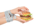 Healthy weight loss diet concept burger cheeseburger in hands with measure tape isolated on white background Stock Images