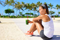 Healthy woman runner drinking green smoothie vegetable resting and relaxing after running fitness and lifestyle concept Royalty Free Stock Images