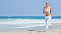 Healthy woman running on the beach girl doing sport outdoor happy female exercising freedom vacation fitness and heath care Royalty Free Stock Images