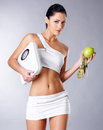 Healthy woman with the scales and green apple. Royalty Free Stock Images