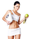 Healthy woman stands with the scales and green apple eating concept Royalty Free Stock Photos