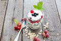 Healthy yogurt dessert with muesli raspberries and black currants on wooden background Royalty Free Stock Images