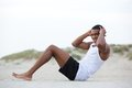 Healthy young man doing sit ups at the beach Royalty Free Stock Photo