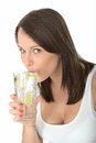 Healthy young woman drinking a glass of fresh iced water dslr royalty free image attractive with lime wedges for hydration Royalty Free Stock Photography