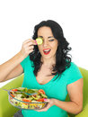 Healthy Young Woman Holding a Fresh Bowl of Mixed Colourful Salad Holding A Cucumber Slice Over Her Eye Royalty Free Stock Photo