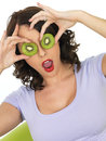 Healthy young woman holding fresh ripe kiwi fruit slices over eyes a dslr royalty free image of attractive sliced with expression Stock Photography