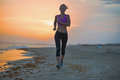 Healthy young woman running on beach in the evening sportswear Stock Image