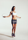 Healthy young woman skipping rope in studio muscular exercising with jumping on grey background Royalty Free Stock Images