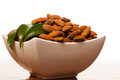 Heap of almonds in white bowl, healthy snack isolated over white Royalty Free Stock Photo