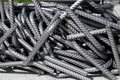 A heap of bent division rebar - curved steel reinforcement bars at a construction site Royalty Free Stock Photo