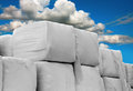 Heap of cubic hay bales wrapped in white plastic on blue sky Stock Images