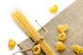 Heap of macaroni shells and spaghetti with rope on brown bagging Royalty Free Stock Photo
