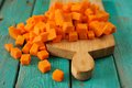 Heap of orange sweet pumpkin cubes on wooden board on turquoise Royalty Free Stock Photo