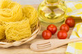 Heap of pasta capellini in wicker basket, tomatoes, vegetable oi Royalty Free Stock Photo
